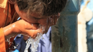 boy drinking water from hands